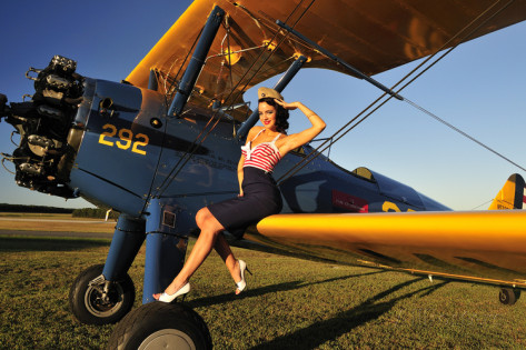 1940-s-style-pin-up-girl-sitting-on-the-wing-of-a-stearman-biplane
